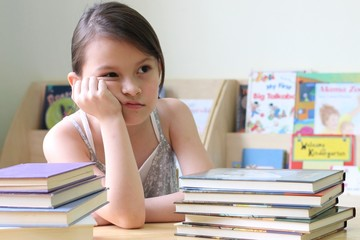 child with books in classroom grumpy face