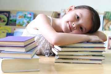 child sleeping on books with happy face