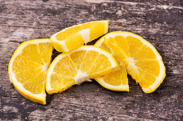 bunch of orange slices on wood background