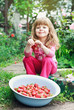 Smiling Girl Holding Bowl of Strawberries