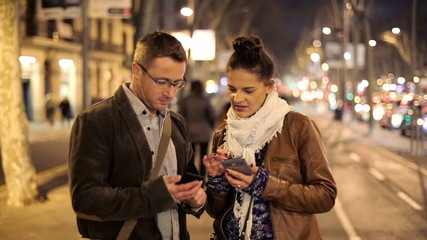 Tourist couple looking at map on smartphone in the city