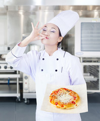 Asian chef and delicious pizza in kitchen