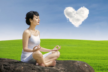 Asian woman exercise yoga under love cloud