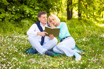 adult couple reading book in the park full of flowers