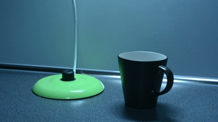 Switching on the kettle with cup on the kitchen counter