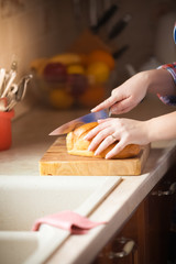 photo of woman cutting bread on wooden desk