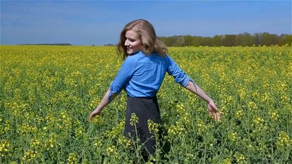 Smiling woman in a field of yellow flowers in a sunny day