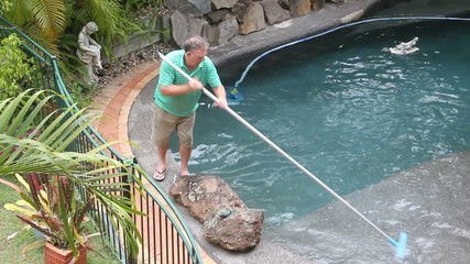 Man cleans the corner his swimming pool with long brush.