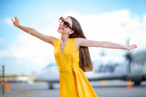 Young woman dressed in yellow dress simulating flight with hands - 64246285