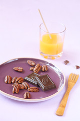 Pecans, chocolate pieces on a purple plate