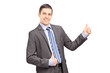 Businessman leaning against wall and giving thumb up