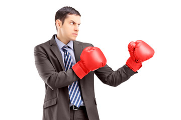 Businessman in suit with red boxing gloves posing