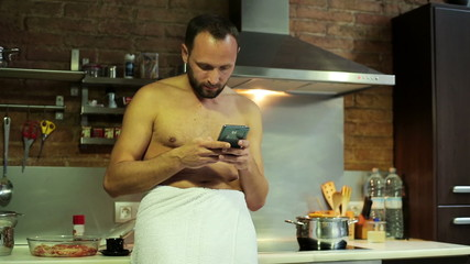 Man texting on smartphone and drinking coffee after shower