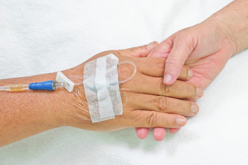 old hands of patients holding each other with IV solution