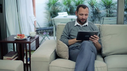 Man with tablet computer drinking tea on sofa at home