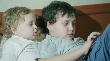 Two young children playing with a tablet