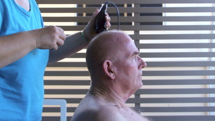 Man getting a close hair cut with hair clippers.