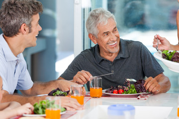 mature man with family dinner table