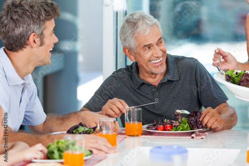 mature man with family dinner table - 64249816
