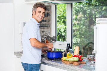 Handsome man cooking at home kitchen smile