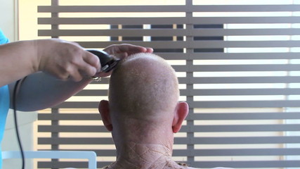 Rear view of a middle aged elderly man getting a close hair cut