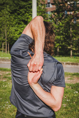 Long haired athlete stretching in a city park