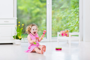 Funny toddler girl playing tambourine in sunny white room