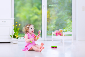Little toddler girl playing tambourine in sunny white room