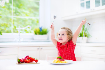 Laughing toddler girl eating spaghetti in white kitchen