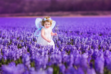 Toddler girl in fairy costume playing in flower field