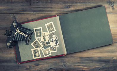 camera and album with old family photos on wooden table