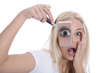 Schockierte Frau sieht durch eine Lupe