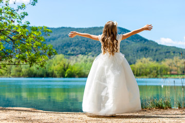Small princess in white dress at lake.
