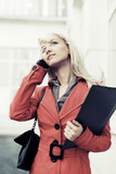 Blond business woman calling on the cell phone against office bu