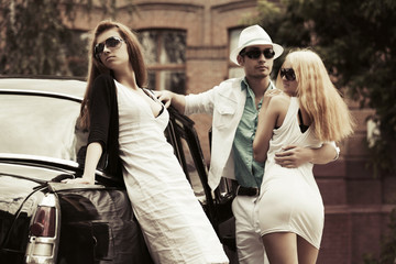 Young couple in love and jealous girl at the retro car