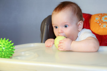 Little baby eating apple and looking at green toy