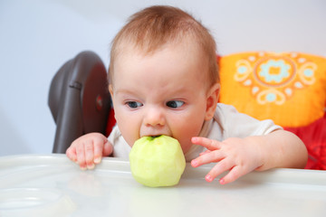 Half-year-old baby sit and bite off pared apple