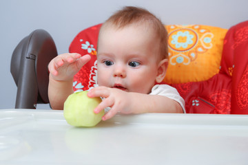 Half-year-old baby sitting and holding pared apple