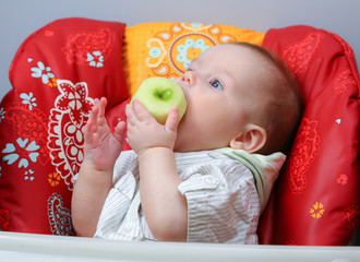Little boy trying to eat pared apple