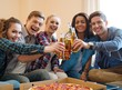 Group of young friends celebrating in home interior