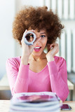 Fototapety Afro woman using newspaper as spyglass