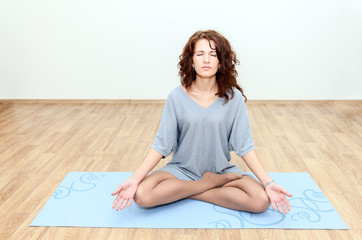 Curly brunette sitting in lotus position on the floor on a mat
