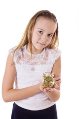 Schoolgirl holding small alarm clock on a white