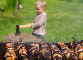Kebabs grilling on a BBQ as a small boy chops wood