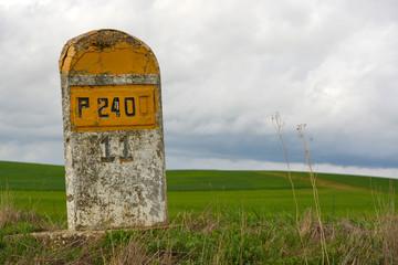 bolardo de piedra señalizando carretera nacional