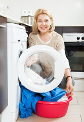Housewife using washing machine at home