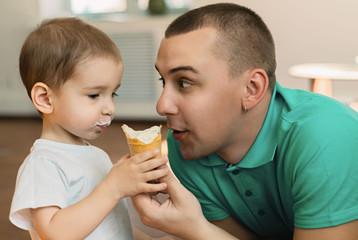 Маленький мальчик в компании папы кушает мороженое