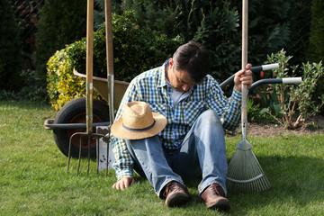 Gärtner beim Pause machen, schläft, hält Rechen