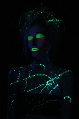 Glowing Woman Wearing UV Cosmetics Under Black Light