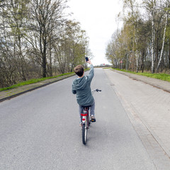 boy shoots a picture while riding bike